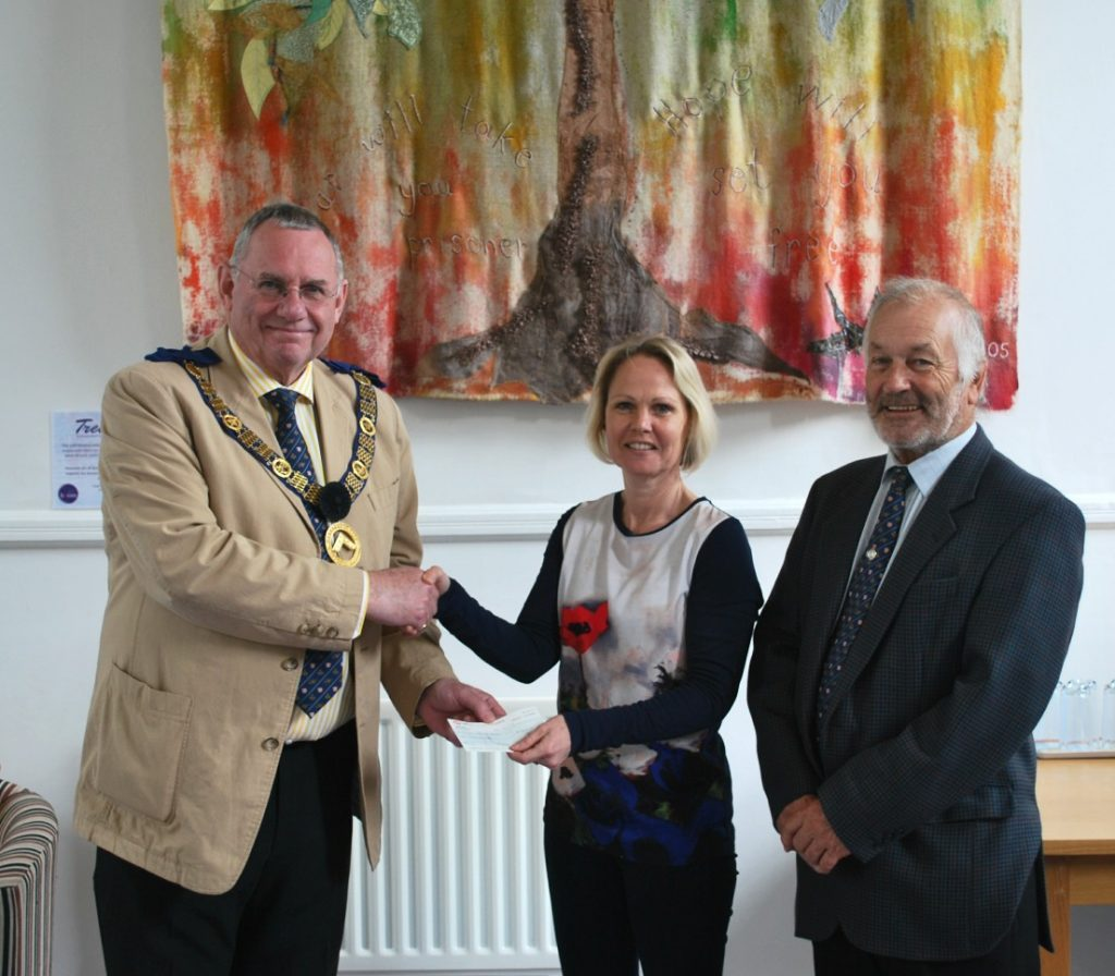 Deputy PGM in Charge, Michael Holland, and Nick Swan, Provincial Charity Steward, present a cheque for £1,000 to Rachael Manacchini-Godfrey of Breast Cancer Haven, Hereford, in front of the Tree of Hope tapestry