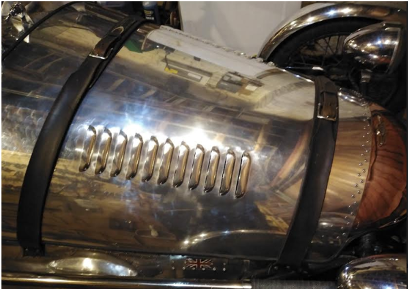 Photo showing the shiny mirrored bonnet of an old style car. Bonnet is held in place by straps.
