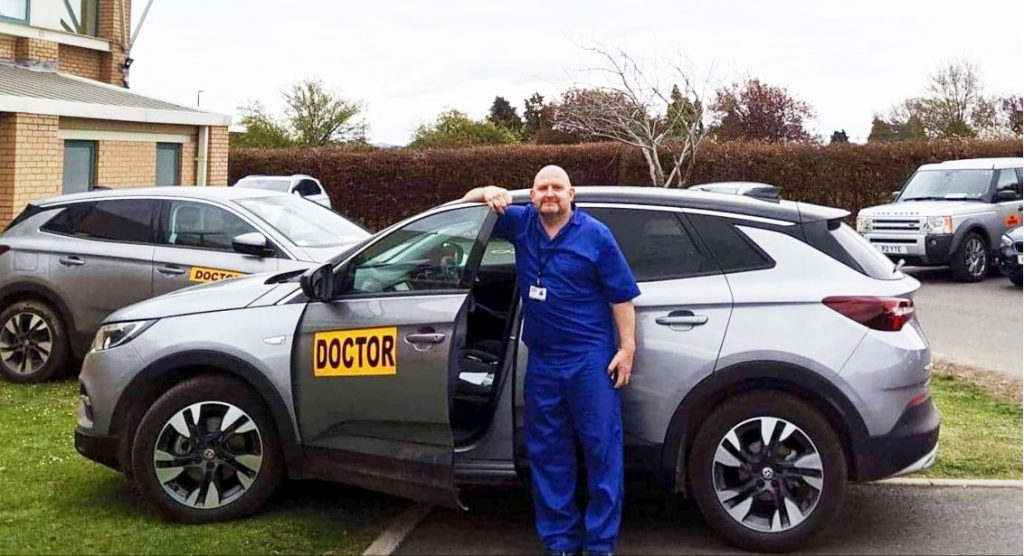 Pete White standing next to a Doctors Car