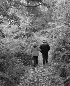Black and white photo of a couple walking away from us along a path through the woods.