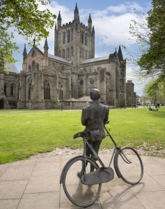 Statue of Edward Elgar leaning against his bike looking at Hereford Cathedral