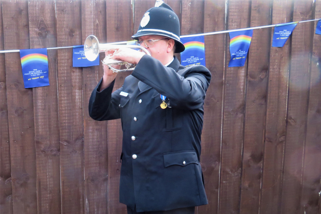 Photo of Policeman playing the Last post in memory of those that lost their lives during the pandemic.