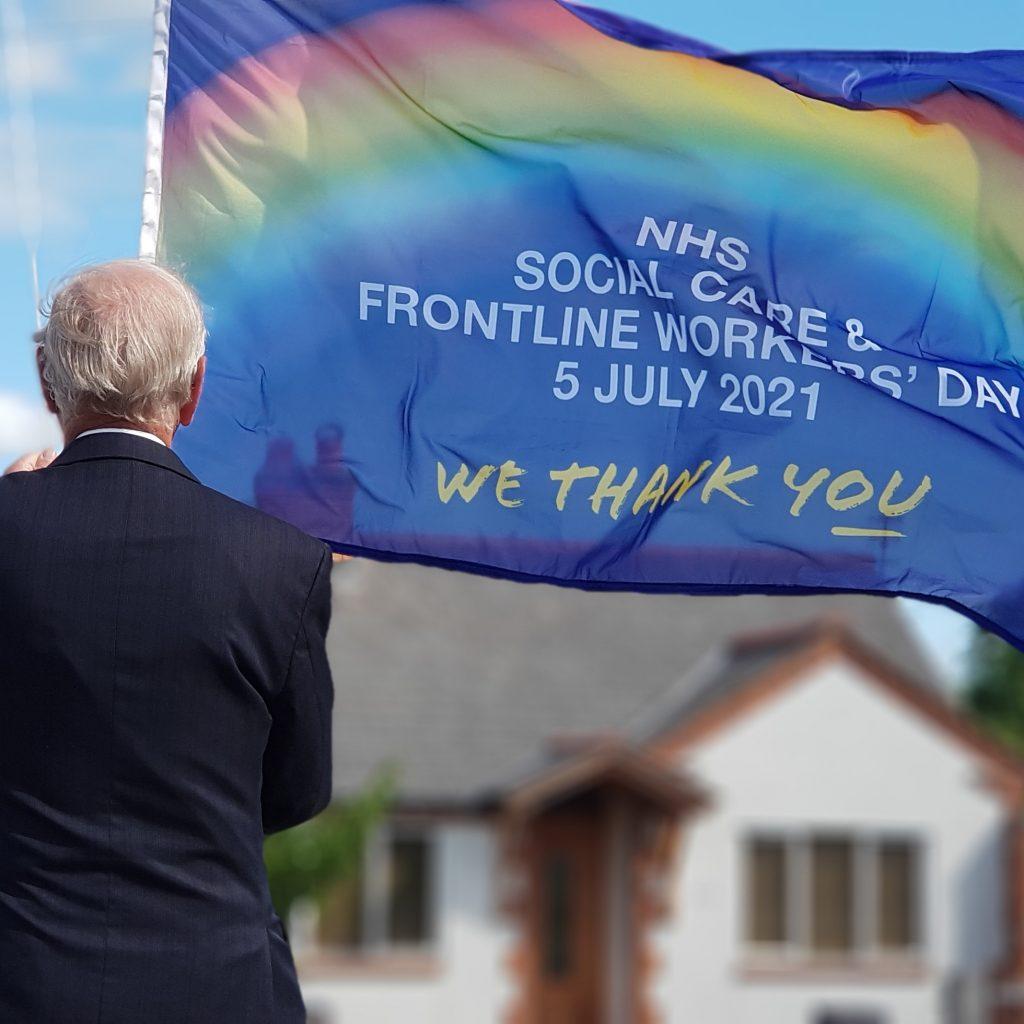 Mason raising NHS Day Flag at Arrow Lodge